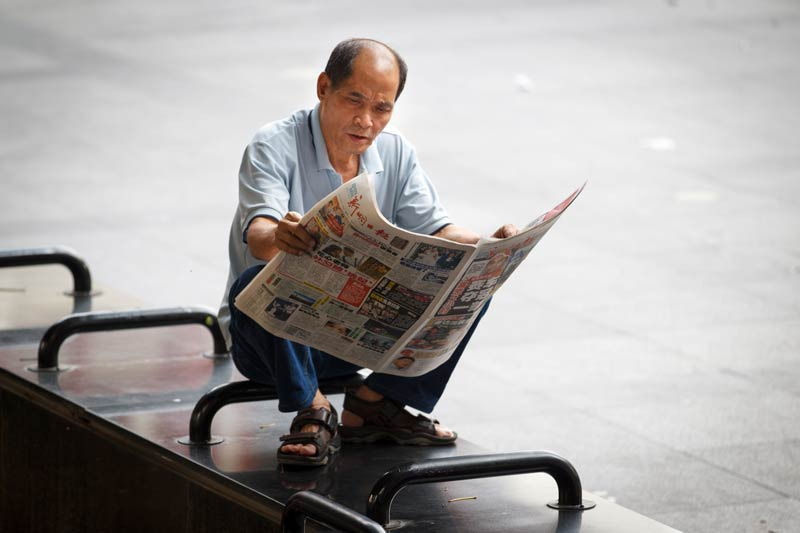 Man crouched down reading a newspaper