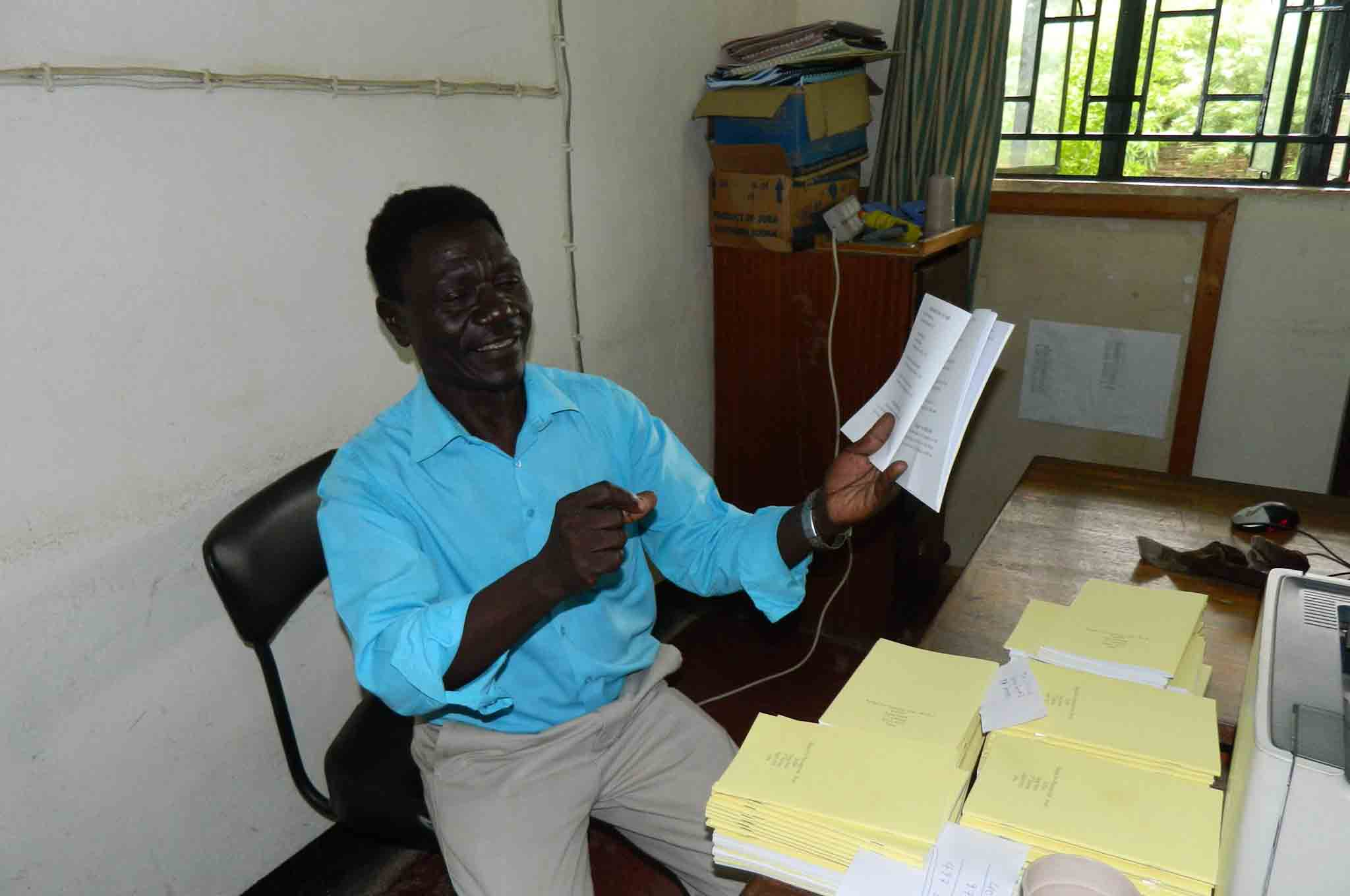 Translator and pastor Enos Dada sings from a Keliko song book.