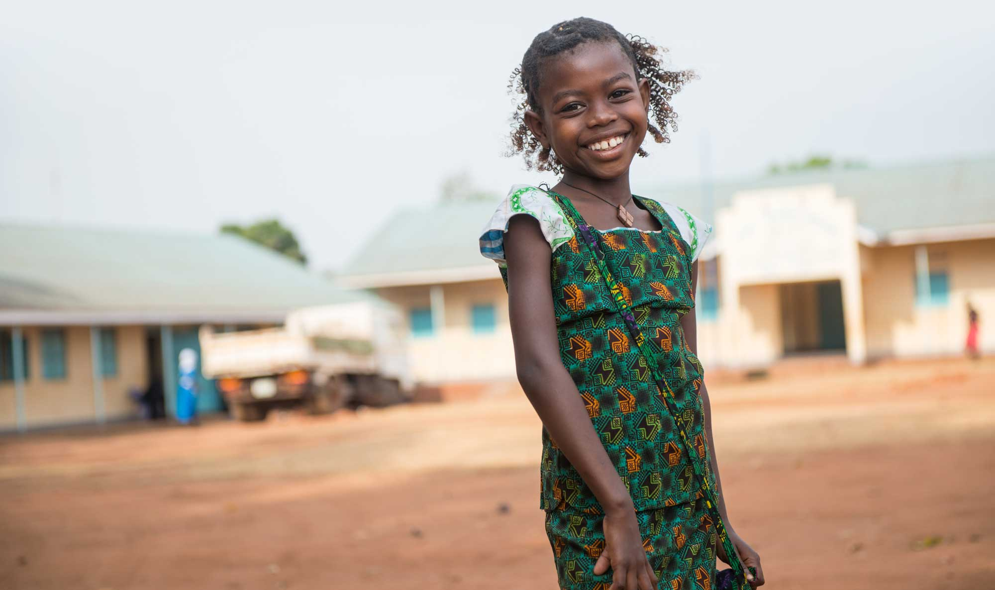 Smiling girl stands in the middle of her South Sudanese village