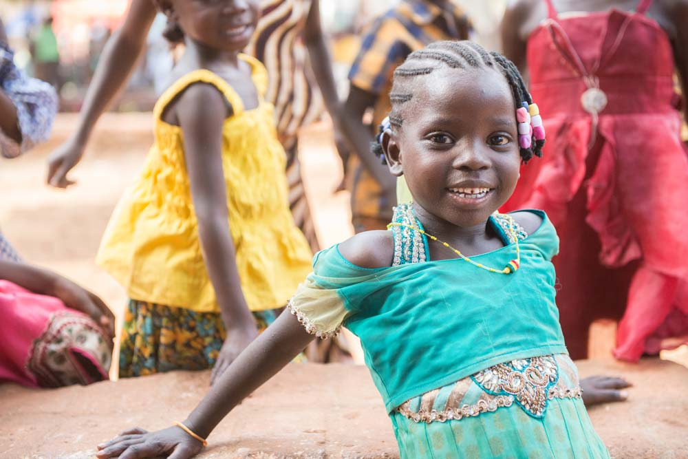 Little girl smiles as she celebrates with her village