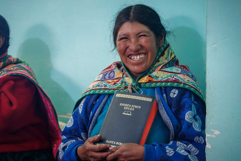 woman grin while holding her New Testament