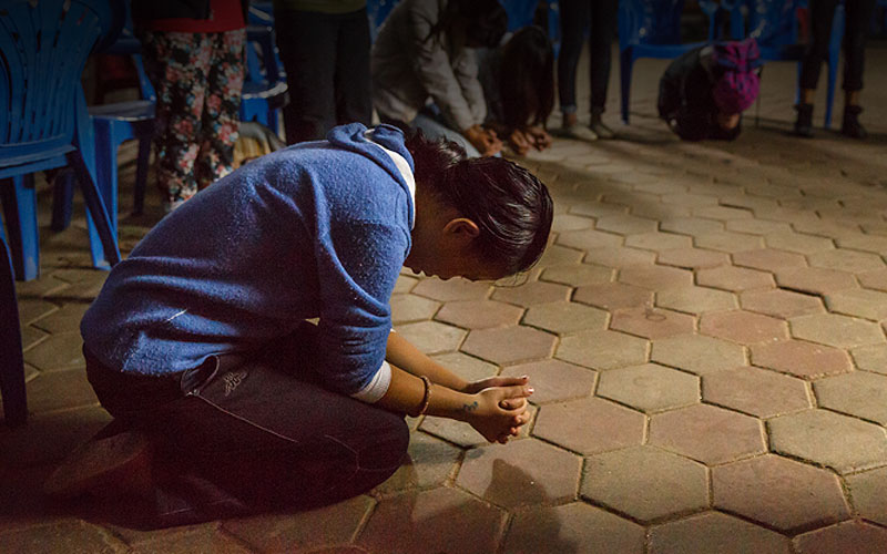 woman on knees, praying