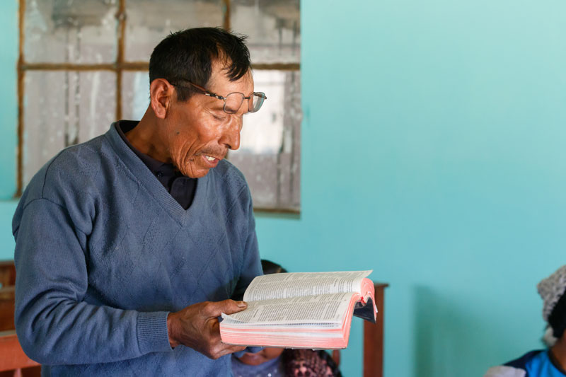Man reads to community group from the Quechua Bible.
