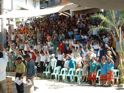 Crowd raising their hands in prayer over the New Testaments