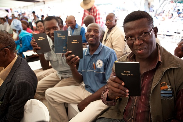 A man smiles as he holds up a Bible