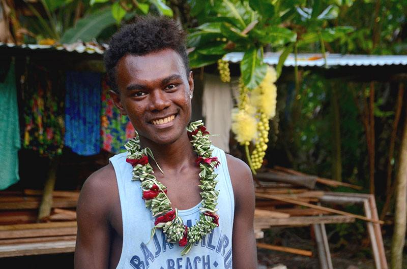 Smiling Roviana young man wearing flower lei from the celebration