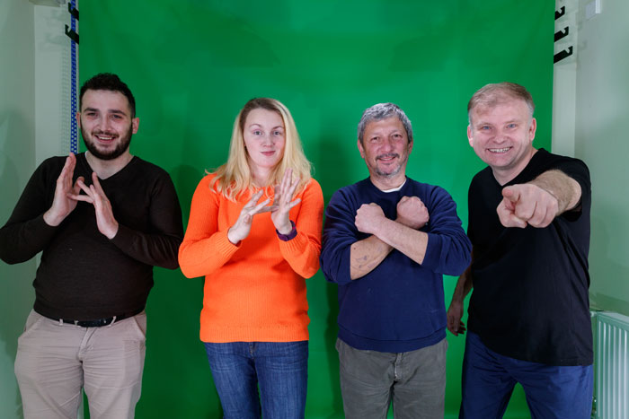 signing 'Jesus Loves You' in Romanian Sign Language