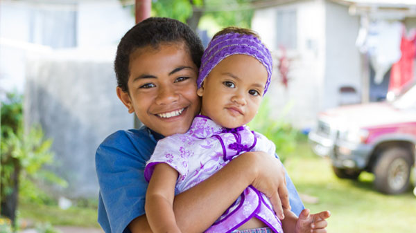 Young Tonga boy holding younger little Tonga girl and smiling for the picture.