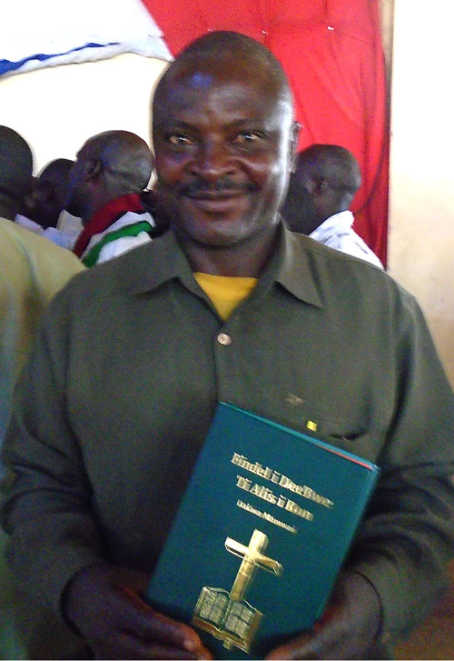 Nigerian man proudly displaying the newly translated Alis i Ron New Testament