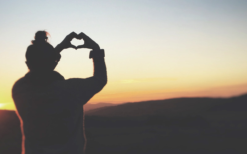 girl making heart symbol with hands, looking at sunrise
