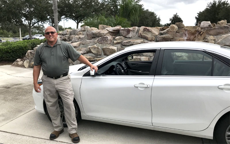 Bill Smith standing next to the 2017 Toyota Camry that he and his wife donated to Wycliffe