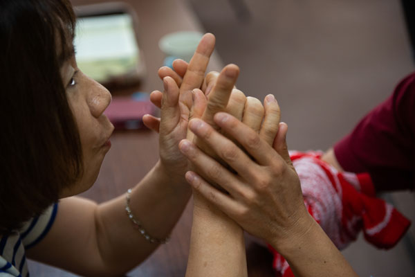 Helping a Deaf and blind woman understand Pastor Matsumoto's sermon.