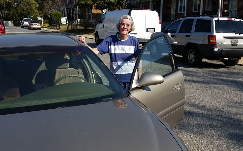 Mary Hildebrand standing by her car