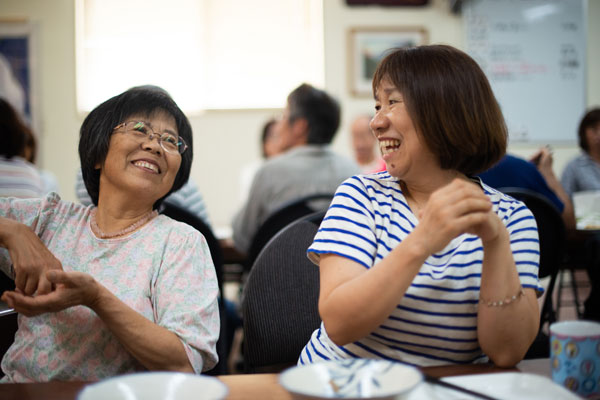Two Japanese women at a lunch table laughing on Sunday morning.