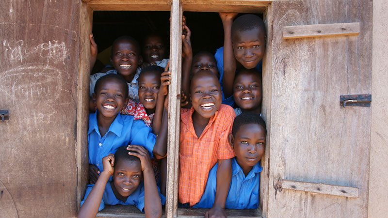 Ugandan students smiling and looking out of their school window