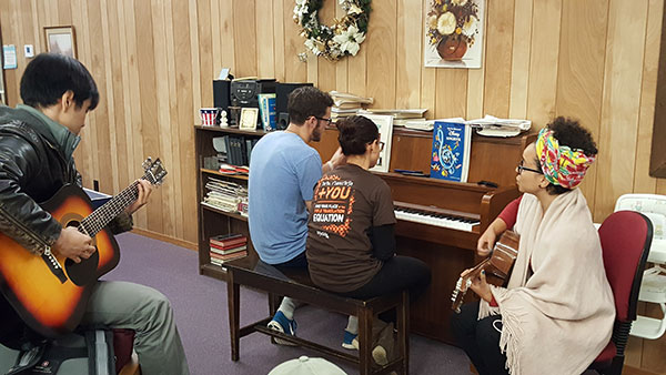 TOTAL It Up! participants worshiping God around a piano
