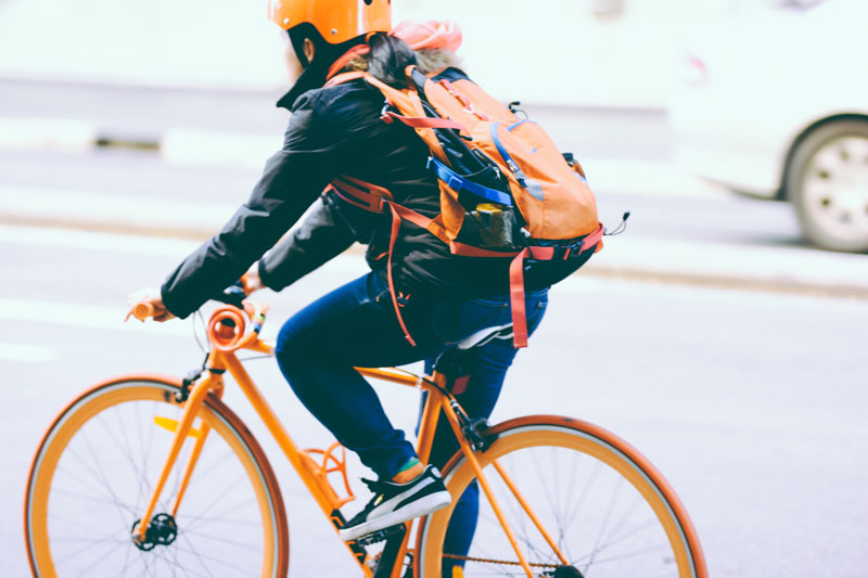 person riding orange bicycle wearing a helmet and backpack