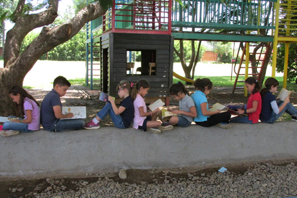 Children reading in groups of two, seated near a playground