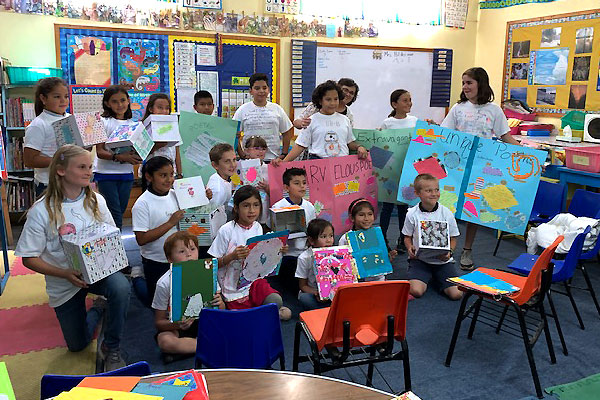 Students in the classroom showing off their artwork