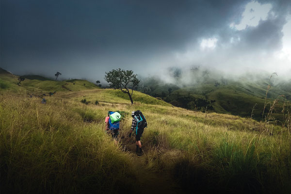 two hikers walking up a steep hillside into a storm