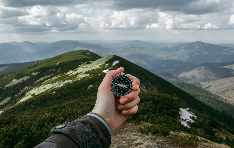 person holding compass up to backdrop of mountain range