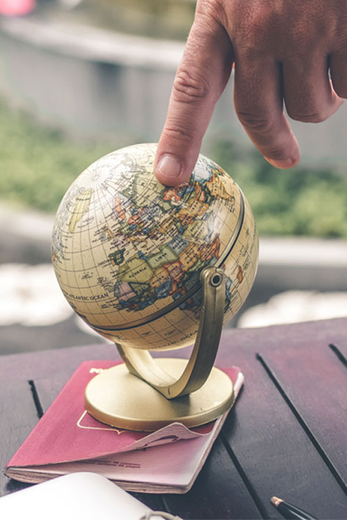 man pointing to small globe on an outside table