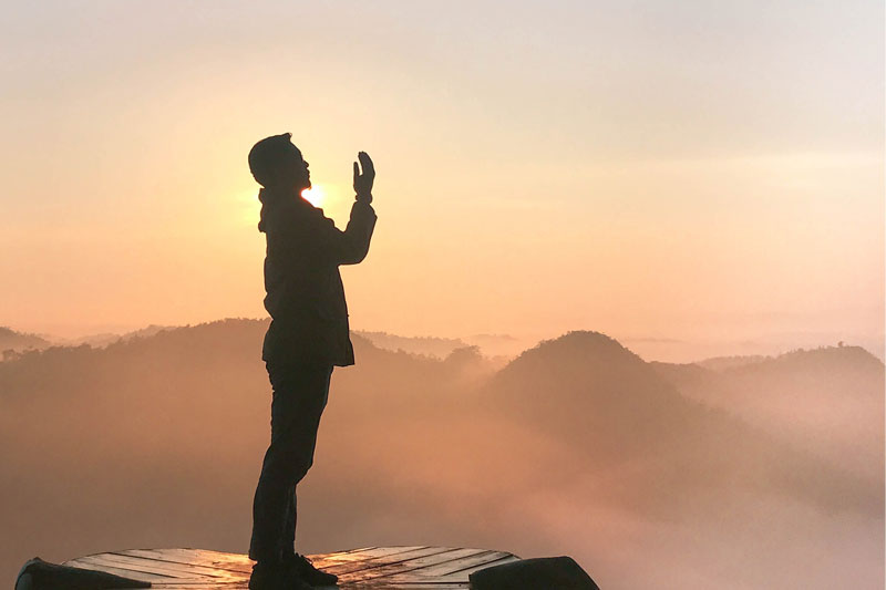 man praying on high platform with clouds in background