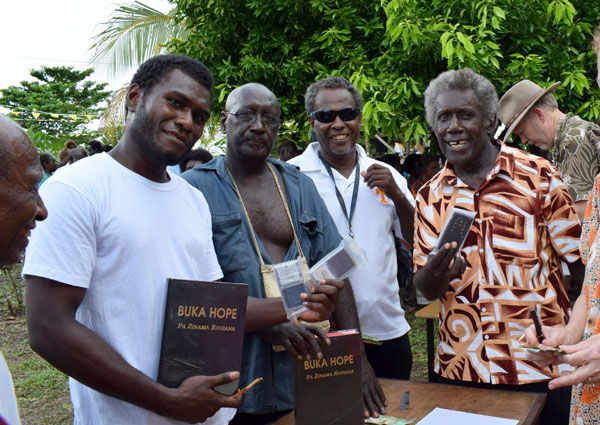 Roviana men buying Bibles and audio New Testament in their language