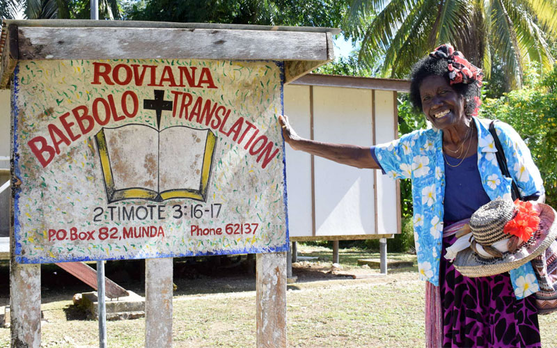 smiling Roviana lady next to Bible translation sign