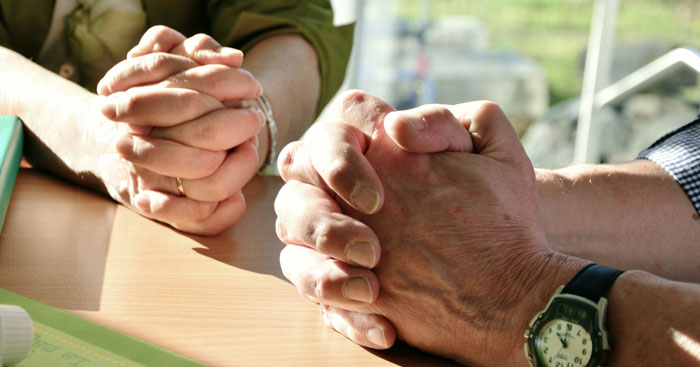 two pairs of hands folded in prayer
